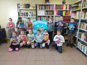 Fotografia przedstawia uczniów klasy 1 pasowanych na czytelnika. W rękach trzymają książkowe upominki.
