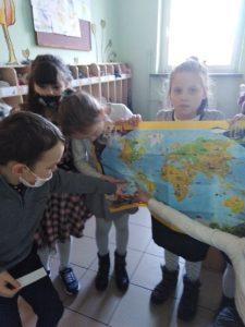 Zdjęcie przedstawia czworo uczniów oglądających mapę świata.