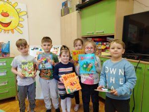"""Zdjęcie przedstawia dzieci 5,6 letnie stojące w sali przedszkolnej, trzymające w rękach nagrody książkowe za konkurs plastyczny """"Ilustracja do baśni""""."""