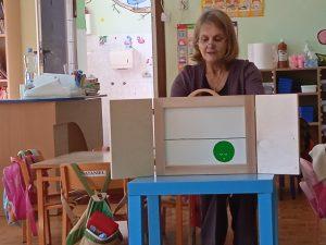 """Zdjęcie przedstawia salę przedszkolną, w której bibliotekarka czyta dzieciom opowieść """"Groszki"""" w teatrze kamisibai."""