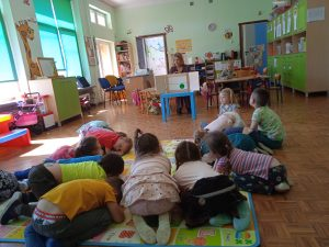 Zdjęcie przedstawia dzieci naśladujące kiełkujące groszki.
