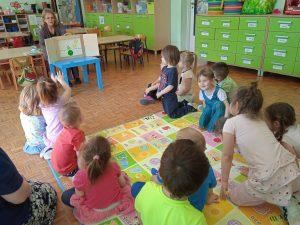 Zdjęcie przedstawia dzieci naśladujące rosnące groszki.