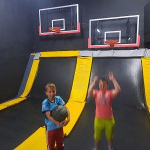Na zdjęciu widać dwóch chłopców grających w koszykówkę