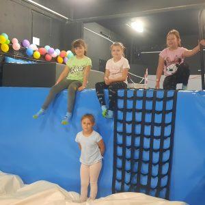 Na zdjęciu widać 4 dziewczynki z klas 1-3. Skaczą do basenu z gąbkami.