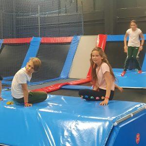 Na zdjęciu widać chłopca i dziewczynkę z klasy 3 siedzących na trampolinie