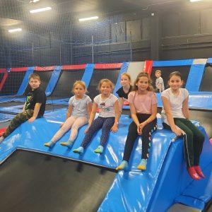 Na zdjęciu widać grupę dzieci siedzących na trampolinach