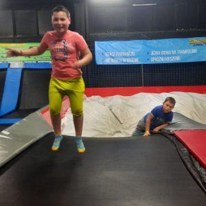Na zdjęciu widać chłopca w trakcie skoków na trampolinie