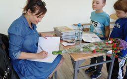 Pisarka wpisuje dedykacje do książek dla dwóch chłopców