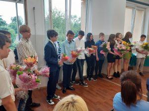 zdjęcie przedstawia ósmoklasistów z bukietami kwiatów
