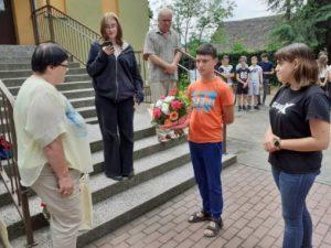 troje uczniów żegna kwiatami nauczyciela