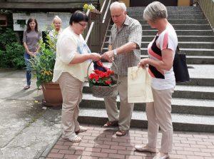 dwoje nauczycieli wręcza nauczycielce kosz z kwiatami