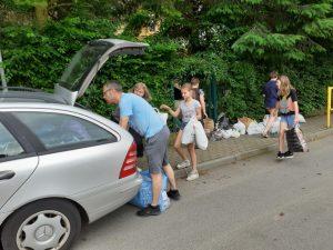 zdjęcie przedstawia rodzica i uczniów pakujących worki z nakrętkami do samochodu