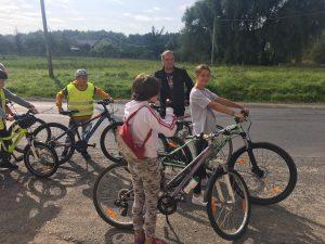 Zdjęcie przedstawia 4 rowerzystów i ich opiekuna odpoczywających przed sklepem w miejscowości Buchałów.
