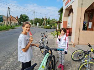 Zdjęcie przedstawia 2 rowerzystki odpoczywające przed sklepem w miejscowości Buchałów.