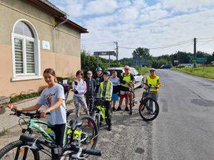 Zdjęcie przedstawia 8 rowerzystów odpoczywających przed sklepem w miejscowości Buchałów.