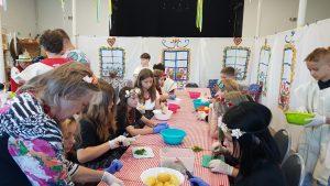 Zdjęcie przedstawia dzieci i seniorów przygotowujących potrawy z ziemniaków.