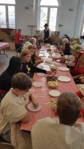 Dzieci przy długim stole kosztują ziemniaczane potrawy.